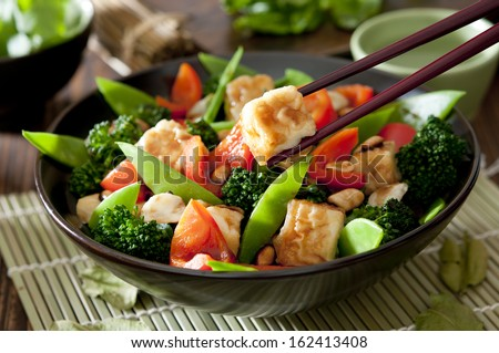 Closeup of a bowl of tofu and vegetable stir fry. - stock photo
