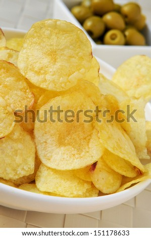 closeup of a bowl with potato chips and a bowl with pitted olives, a typical spanish appetizer