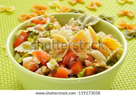 closeup of a bowl with refreshing pasta salad on a draped table with a green tablecloth