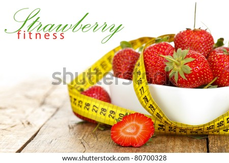 Closeup of a bowl with strawberries and a measure tape with place for your text on the left