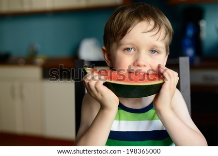 Closeup of a boy eating watermelon at home - stock photo