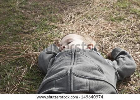 Closeup of a boy taking a nap on grass - stock photo