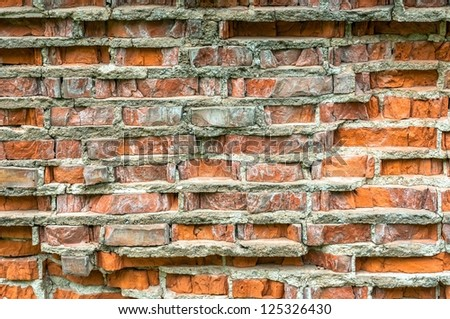 Closeup of a brick wall with cracked surface