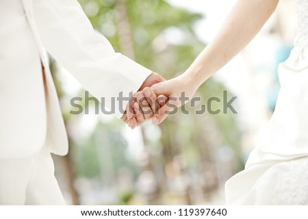 Closeup of a bride and groom holding hands - stock photo