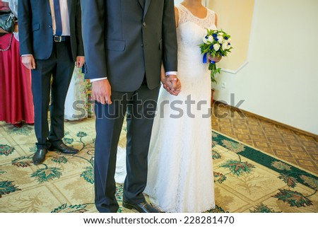 Closeup of a bride and groom holding hands isolated over a white background. - stock photo