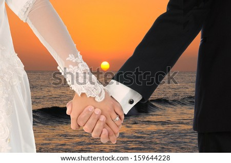 Closeup of a bride and groom holding hands with a beautiful sunset over the ocean in the background. - stock photo