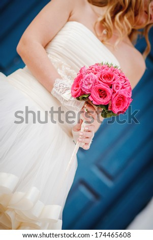 closeup of a bride in white dress holding her wedding bouquet