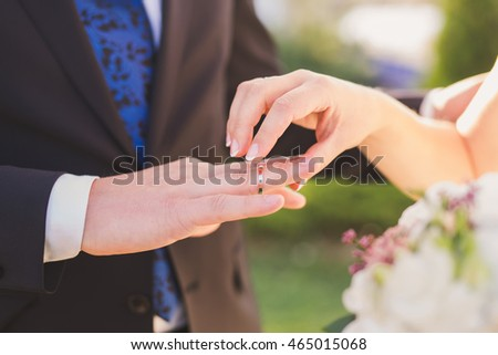 closeup of a bride put a wedding ring onto the groom's finger