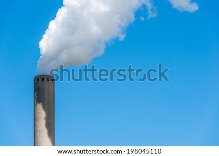 Closeup of a bright blue sky with white polluting smoke from a high chimney.