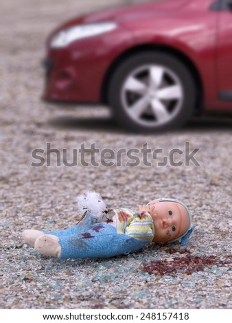 Closeup of a broken doll and bleeding on the asphalt and broken glass of a vehicle. - stock photo