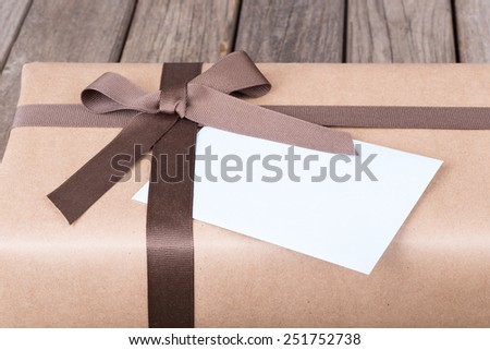 Closeup of a brown gift box tied in ribbon and bow - stock photo