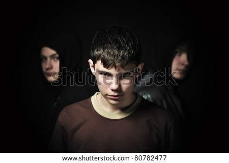 Closeup of a brunette teenager with his friends barely visible in the background - stock photo