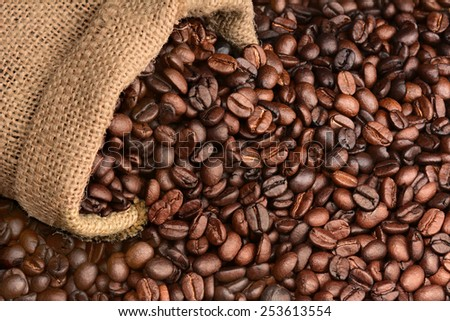 Closeup of a burlap sack of fresh roasted coffee beans spilling onto a table. The beans fill the frame. Horizontal format. - stock photo