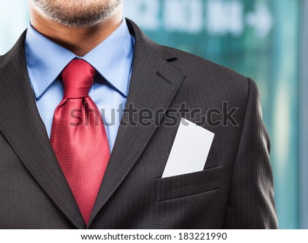 Closeup of a business card in a businessman's suit - stock photo