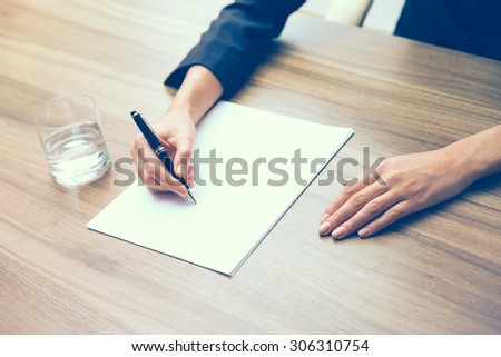 Closeup of a business woman's hands while writing down some essential information. A glass of water, paper and a pen. A concept of drafting the contract. Toning filter. - stock photo