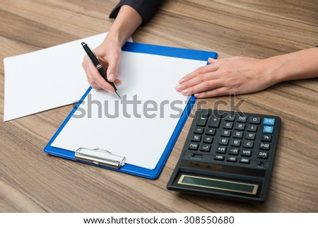 Closeup of a business woman's hands while writing down some essential quantitative information. Calculating machine, paper and a pen. Toning filter. - stock photo