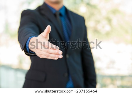 Closeup of a businessman extending his hand for a handshake - stock photo