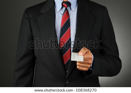 Closeup of a businessman handing a credit card. Horizontal format over a light to dark gray background.