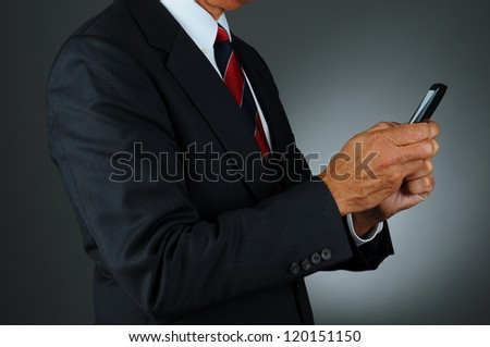 Closeup of a businessman in a dark suit against a light to dark gray background using his cell phone to send a text. Man is unrecognizable and seen from the side. - stock photo