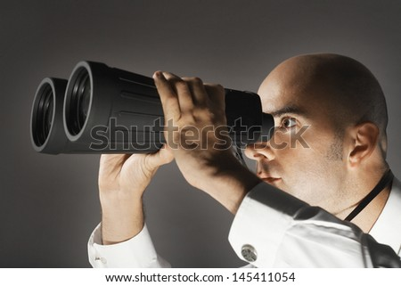 Closeup of a businessman looking through large binoculars against gray background - stock photo