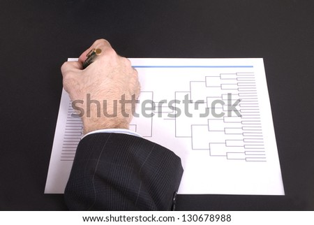 Closeup of a businessman's hand holding a pen completing tournament bracket - stock photo