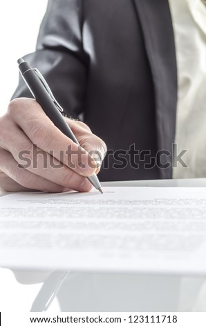 Closeup of a businessman's hand signing a contract on a white desk with reflection. - stock photo