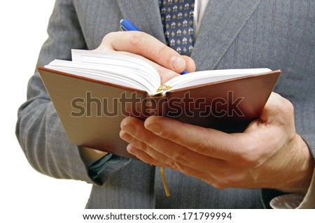 Closeup of a businessman taking notes in a small notebook. Hands and torso only. In white background. - stock photo
