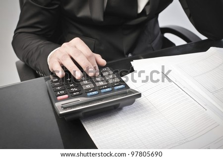 Closeup of a businessman using a calculator - stock photo