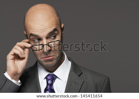 Closeup of a businessman with hand on glasses making a face against gray background - stock photo
