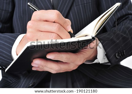 closeup of a businessman writing in a notebook - stock photo