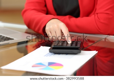 Closeup of a businesswoman hands accounting with calculator sitting in a desktop at office with her red suit in the background - stock photo
