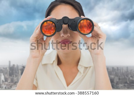 Closeup of a businesswoman looking through binoculars against cityscape