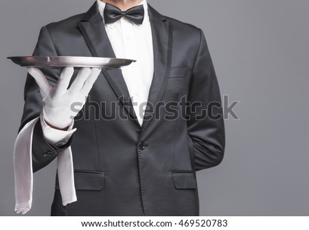 Closeup of a butler holding a silver tray on gray background