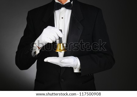 Closeup of a butler wearing a tuxedo and holding a service bell in front of his torso. Man is unrecognizable. Horizontal format on a light to dark gray background. - stock photo
