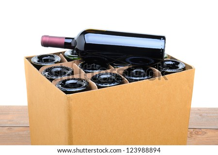 Closeup of a case of wine with one bottle resting on top. Case is sitting on a wood table top with a white background. - stock photo
