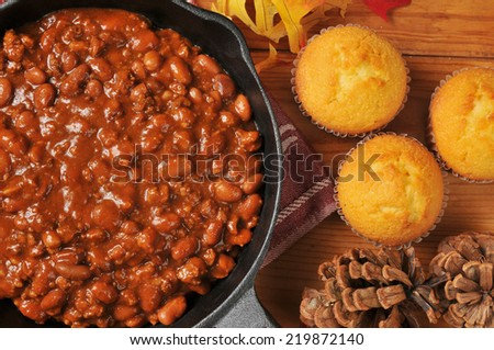 Closeup of a cast iron skillet of chili con carne with corn bread muffins, shot from a high angle view - stock photo