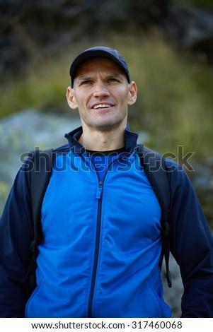 Closeup of a caucasian hiker man with backpack, selective focus - stock photo