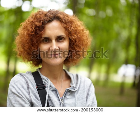 Closeup of a caucasian redhead woman outdoor in the park - stock photo