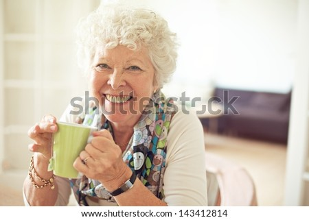 Closeup of a charming old lady drinking her tea - stock photo