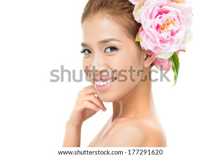 Closeup of a charming young woman with a pink flower in hair looking at camera  - stock photo