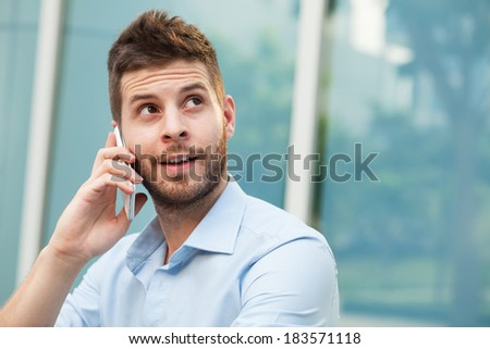 Closeup of a cheerful businessman communicating by smartphone