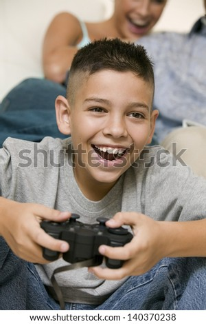 Closeup of a cheerful little boy playing video games with happy blurred mother in the background at home