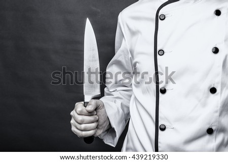 Closeup of a chef  holding a big sharp knife over gray background - stock photo