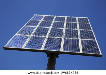 closeup of a chess board pattern of solar panels close together and blue sky