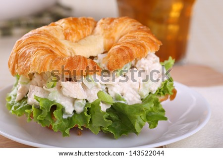 Closeup of a chicken salad and lettuce on a croissant roll - stock photo