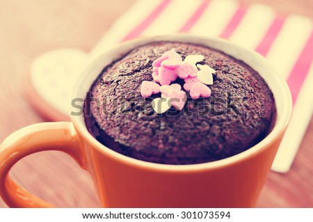 closeup of a chocolate mug cake topped with heart-shaped confetti sprinkles placed on a set table, with a filter effect - stock photo
