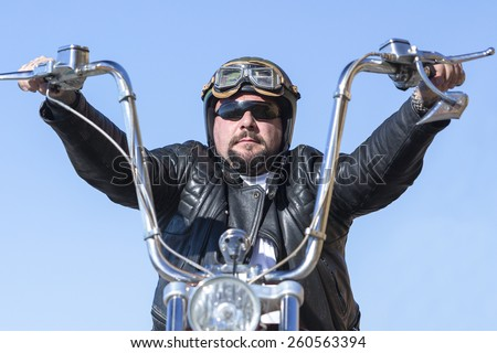 closeup of a chopper motorcyclist riding his customized motorcycle by a mountain road at sunrise - focus on the face