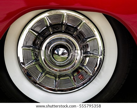 closeup of a chrome hubcap with a whitewall tire on a red car at a car