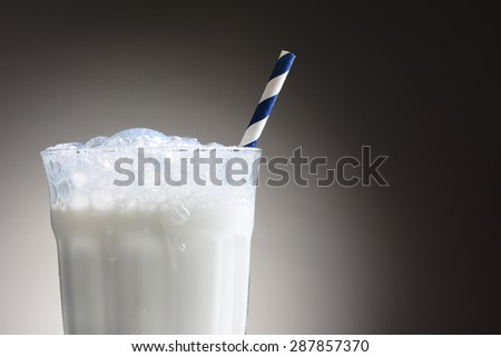 Closeup of a cold glass of milk with a blue and white striped drinking straw. The milk glass has a frothy top with bubbles running down the outside. Horizontal over a light ot dark gray background. - stock photo