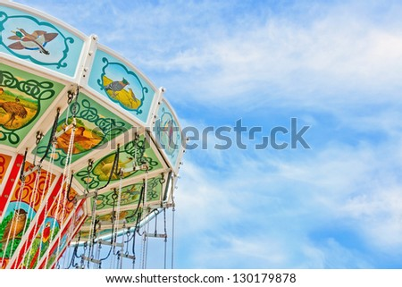 Closeup of a colorful carousel with blue sky background and copy space - stock photo